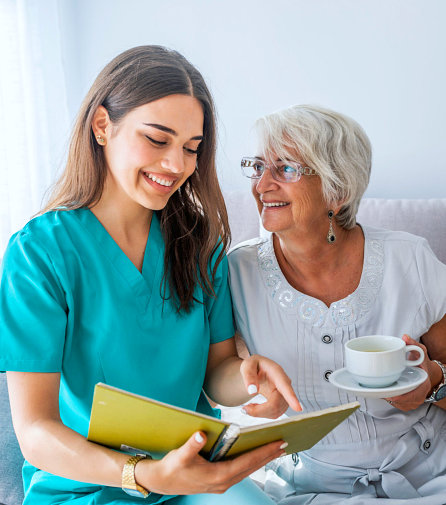 caregiver and senior woman wearing eyeglasses smiling