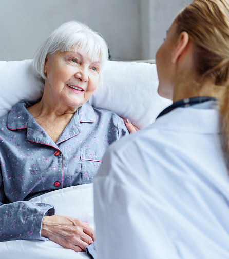 caregiver and senior woman lying in the smiling