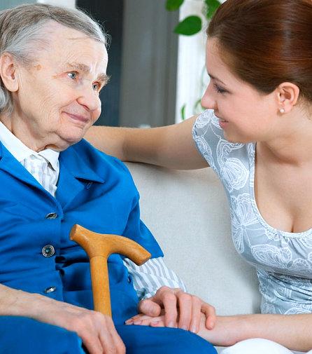 caregiver looking at a senior woman smiling