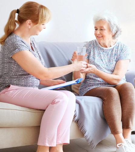 caregiver give a glass of water to senior woman smiling