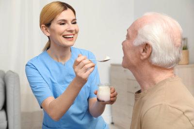 caregiving giving food to elderly