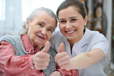 caregiver and elderly giving a thumbs up